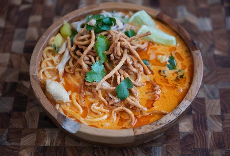 One of the dishes on the take-out menu is Chef Techamuanvivit's signature northern-style khao soi—springy egg noodles, shredded chicken, pickled mustard greens, and chili oil. Photo Credit: Colin Peck