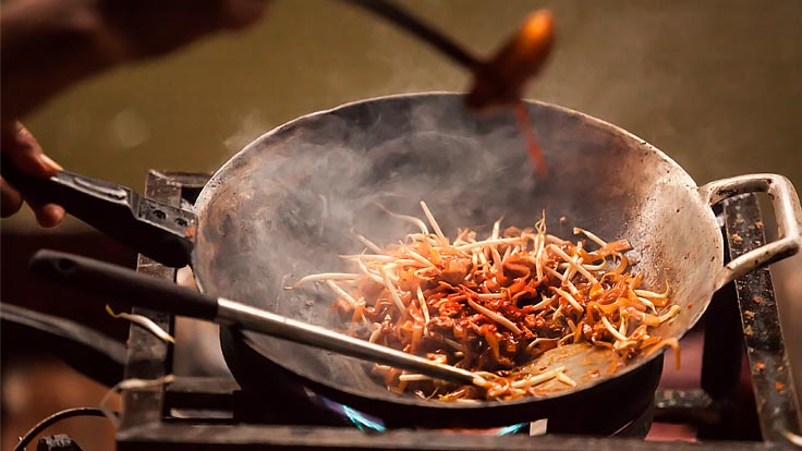 Phad thai cooking in a hot wok. (© Shutterstock)