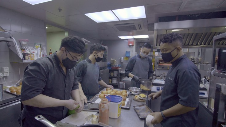 Chef de cuisine Sufian (far right) and the Alma team putting together their best-selling burgers in the kitchen