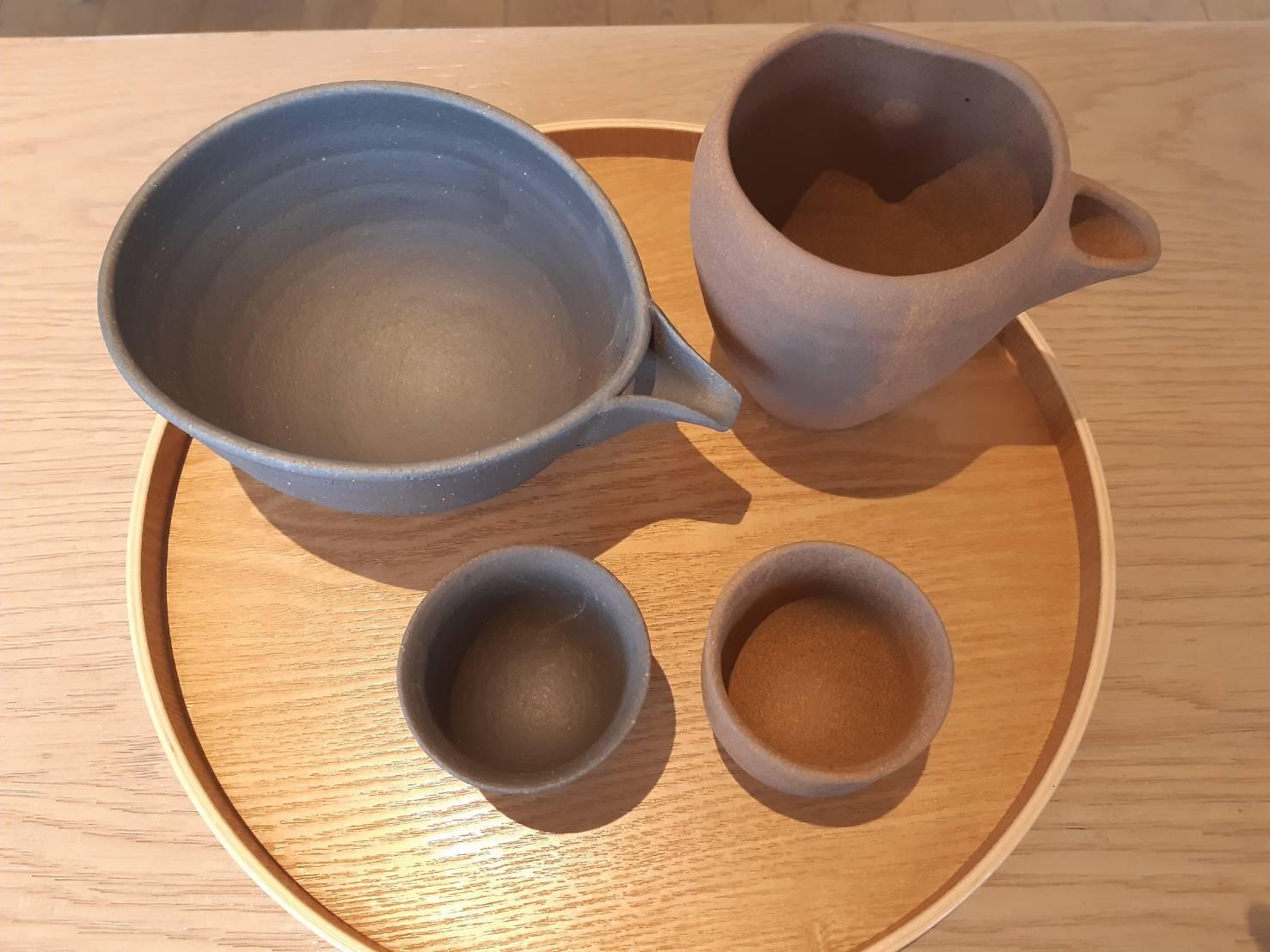 陶製的片口、德利與清酒杯。(謝明玲攝)