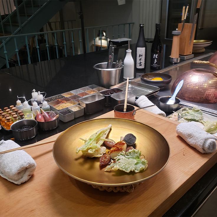 Le plat préparé par le chef : coquille Saint-Jacques caramélisée avec un vinaigre de Xérès, bouillon de haddock, ail noir. ©C.Sirdey/MICHELIN