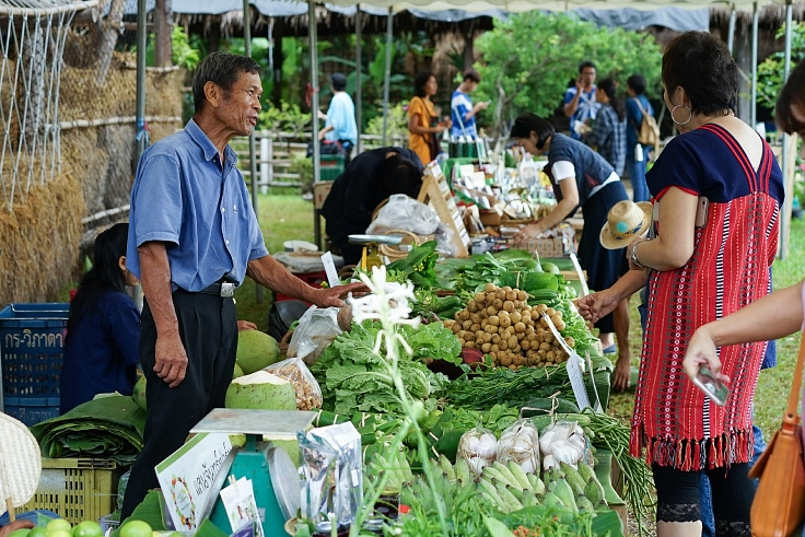 A local farmer with customers at Ginger Farm. (© Tina Hsiao / MICHELIN Guide Thailand)