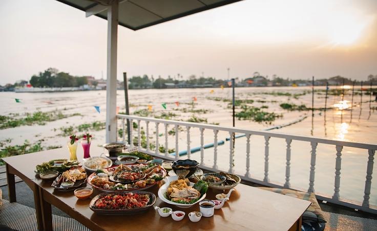 ศาลาริมน้ำของร้านคือจุดที่ทิวทัศน์ยอดเยี่ยม เห็นทั้งวิวเจดีย์และพระอาทิตย์ตกดินอันงดงาม (© อนุวัฒ เสนีวงศ์ ณ อยุธยา / MICHELIN Guide Thailand)