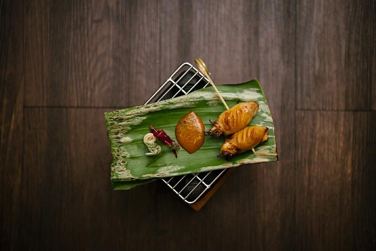 Grilled squid with 20 Eastern Thai herbs. (Anuwat Senivansa Na Ayudhya / MICHELIN Guide Thailand)