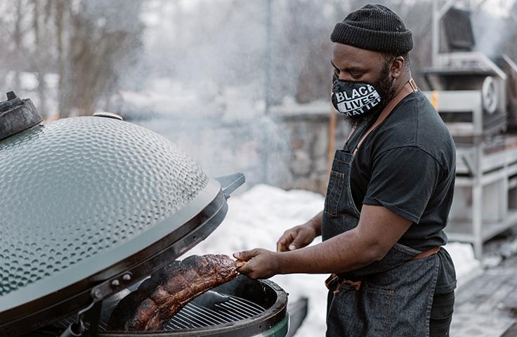 Chef Omar Tate preparing goat ribs. Photo by Elena Wolfe, courtesy of Stone Barns Center