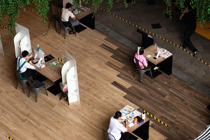พนักงานร้านอาหารในห้างสรรพสินค้าที่จำต้องออกมาตั้งโต๊ะขายเมื่อร้านนั่งรับประทานไม่ได้ (© GroovyPanda/ Shutterstock)