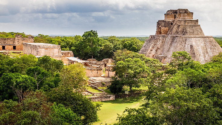 Mayan archaeological site of Uxmal with the Pyramid of the Magician on the right. Photo © Photo Beto/iStock