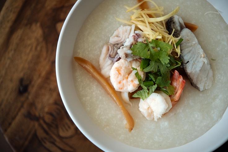 """""""โจ๊กทะเล"""" เนื้อเนียนละเอียด นอกจากใช้ของสดแล้วเคล็ดลับความอร่อยของโจ๊กร้านนี้คือข้าวกลางปี (© อนุวัฒ เสนีวงศ์ ณ อยุธยา/ MICHELIN Guide Thailand)"""